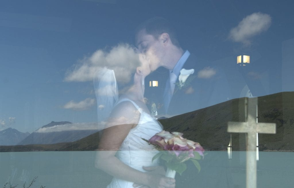 Couple kiss during wedding in the Church of the Good Shepherd at Lake Tekapo