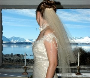 Bride looking through the alter window during her wedding in the Church of the Good Shepherd in Lake Tekapo.