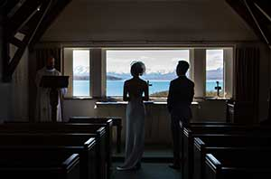 Gege and NaiSong look through the altar window at the Church of the Good Shepherd during their Lake Tekapo Wedding